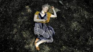 Viivi Sihvonen makaa maassa, silmät ummessa, ympärillä lehtiä ja sammalta.