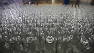 Veen veden tyhjiä pulloja rivissä.
