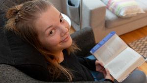 Ylioppilas Lotta Yli-Hukka-Siira lukee kirjaa.