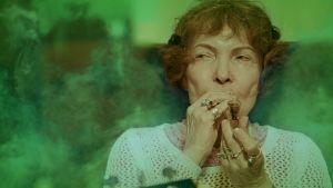 Sirkka Linder polttaa pilveä, vihreä savupilvi leijailee ympärillä.