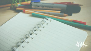 Kuvassa on erilaisia kyniä ja tyhjä vihkoaukeama pöydällä.