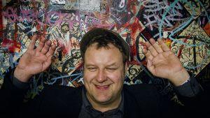 Joose Berglund kädet ylhäällä graffitiseinän edessä