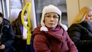 Yolanda med en vit mössa och frånvarande min på tunnelbanan.