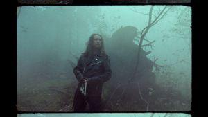 Kriitikko Toni Jerrman sumuisessa metsässä kädessään Stalker-elokuvan mallinen isoon mutteriin sidottu kangasriekale.