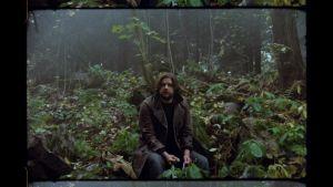 Toimittaja Valtteri Mörttinen istuu aluskasvillisuuden keskellä syksyisessä metsässä kädessään Stalker-elokuvasta tuttu mutteriin sidottu kangasriekale.