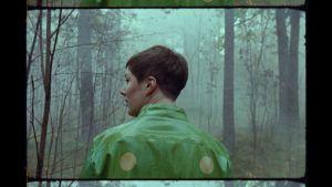 Toimittaja Anna Möttölä vihreässä sadetakissa katsoo sivulleen selin kameraan sumuisessa metsässä.