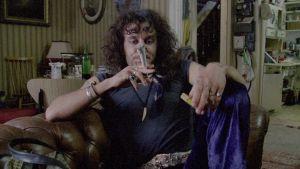 """Huumekauppias-Danny (Ralph Brown) polttelee jättiläismäistä marihuanasätkää (""""Camberwellin porkkanaa"""") elokuvassa Onnen kiertolaiset (Withnail and I)"""