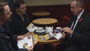 Liberaldemokratiska kandidaten John Skipworth planerar sin kampanj tillsammans med två medhjälpare. Skipworth är en man i senare medelåldern. Sällskapet sitter på ett café.