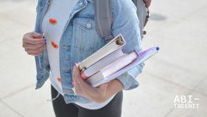 Opiskelija koulukirjoja kainalossa.