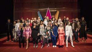 Alla 28 artister på rad med Melodifestivalens logga bakom sig.