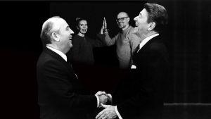 Gorbatsov och Reagan skajar hand och mellan dem i bakgrunden gör Sofie gammals och Lasse Grönroos high five med varandra. Alla fyra skrattar.