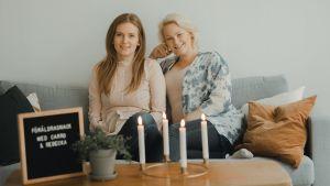 Två kvinnor sitter i en soffa och ler. De är båda gravida.