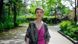 Nuori nainen katsoo kameraan ja hymyilee, taustalla katu ja puistoa.