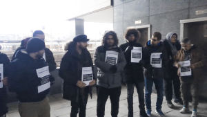 En grupp män står utomhus. De har papperslappar i handen.
