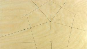 En pentagon ritad på trä.