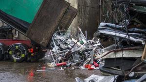 Kuorma-auto kippaa metalliromua maahan.