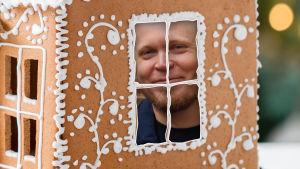 Kike Bertell tittar ut genom fönster på pepprkakshus.
