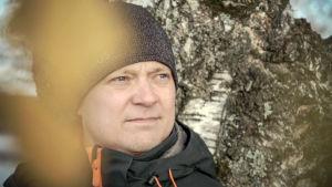 Ville Naumanen lähikuvassa. Seisoo koivun juurella.