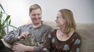 Ville ja Tiina Naumanen istuvat sohvalla. Villellä on sylissään kissa.