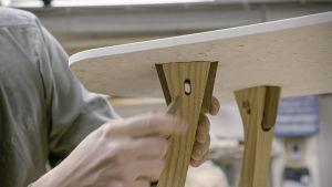 Ville Naumanen asettaa kiilaa pöydän jalan liitokseen.
