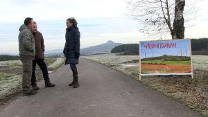 Tyska aktivister intill ett plakat där man motsätter sig vindmöllorna.