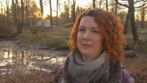 Maria Mäkinen, en dam med rött, lockat hår, står vid en uttorkad damm.
