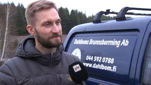 Kristian Dahlbom, en man med skägg och mustasch, står farmför en blå bil med texten Dahlboms brunnsborrning.