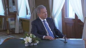 President Sauli Niinistö sitter vid ett bord med en blomma och en mikrofon framför sig. Bilden visar honom snett framifrån och han tittar ut genom fönstret.