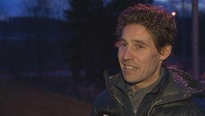 Kari Mattila, en medelålders man med ganska kort brunt hår och en vinterjacka står utomhus. Det är skymning.