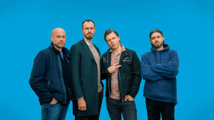 Neljä miestä seisoo sinistä taustaa vasten.