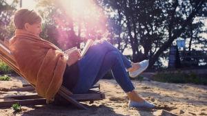 Nainen istuu aurinkotuolilla hiekalla kesäisessä auringonvalossa.