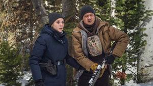 Nainen ja mies metsässä, miehellä pyssy. Katsovat eteensä hätääntyneen näköisinä.