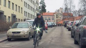 En man cyklar längs med en väg och signalerar sväng till vänster med handen.
