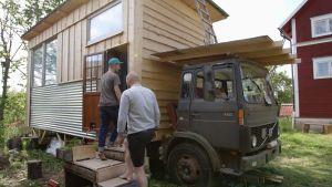 David Roxendal och Matias Jungar på väg in i ett mikrohus på ett lastbilsflak.