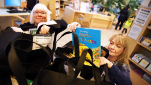 Kaksi naista pakkaa lastenkirjoja isoihin kasseihin