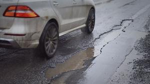 en bil kör förbi en lång och djup beläggningsskada