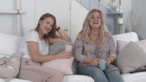Iida ja Nelli istuvat sohvalla ja nauravat.