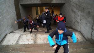 Glad barn springer upp för en tunnel och en redaktör med en mikrofon i handen står mitt i bild och ser glad ut.