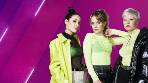 UMK-finalisti F3M-yhtye seisoo UMK:n purppuranvärisen grafiikan edessä. Kolme nuorta naista on pukeutunut neonvihreään ja mustaan, ja he katsovat itsevarmasti kameraan.