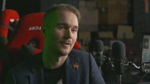 John Kronberg sitter framför en speldator med en mikrofon framför sig.