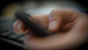 Händer som håller i en mobiltelefon. Fotograferat från sidan.