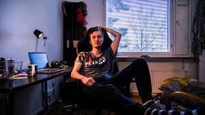 Nuori mies, Aaron, istuu tietokonetuolillaan ja katsoo suoraan kameraan.