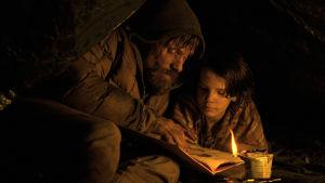 Mies ja poika hämärässä valossa katsovat istualtaan jotain asiakirjaa.
