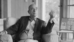 Jörn Donner, en äldre man med kort hår sitter i skjorta och kavaj i en fotölj med randigt tyg. I bakgrunden syns fönster mot en trädgård.