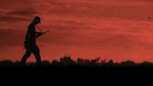 Gerillasoldat går vid röd himmel.