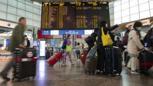 Resenärer med kappsäckar går på Helsingfors-Vanda flygplats. I mitten syns avgående flyg på en tavla.