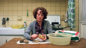 Näyttelijä Delphine Seyrig istuu keittiön pöydän ääressä ja kuorii perunoita. Kuva elokuvasta Jeanne Dielman.
