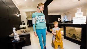 nainen ja lapsi, joka keinuu keinuhevosella. Naisen paidassa lukee I´m a Luxury.