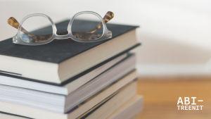 silmälasit kirjapinon päällä