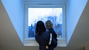 Johanna Pihlajamäki selin, poika sylissä, katsovat ikkunasta